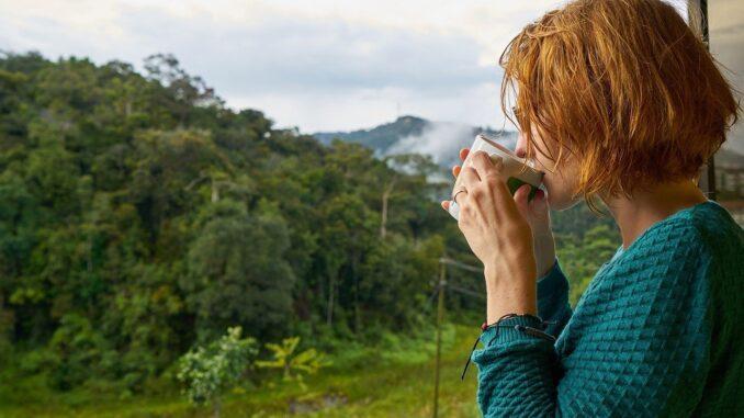 žena z profilu pije raní kávu na balkoně