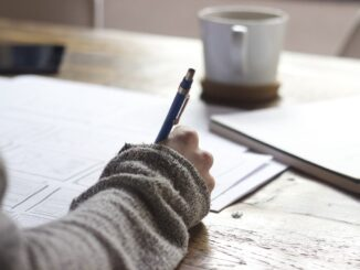 Ruka drží pero a píše na stole, kde je položena káva nabílý papír.