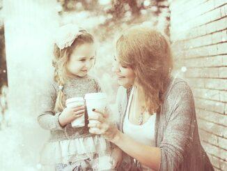 Matka s dcerou mají kávu v platovém kelímku při procházce.