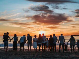 Početná skupina lidí na břehu moře, kde zapadá slunce