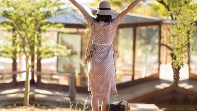 Žena s kufrem a kloboukem je nadšená, že cestuje.