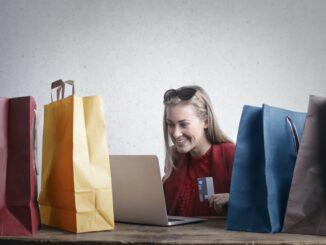Žena s nákupními taškami u počítače.