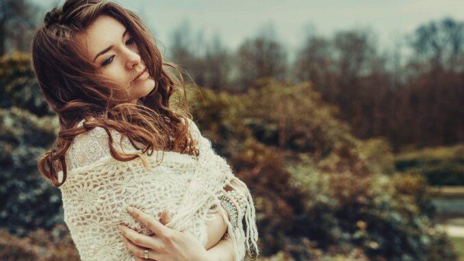 mladá ženy zabalená do vlněného šátku se zamyšleným výrazem