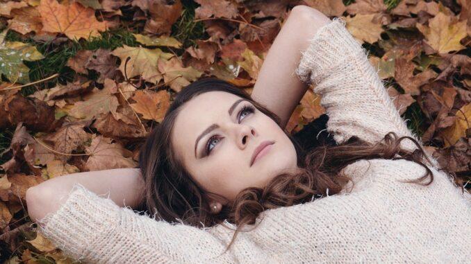 Dívka s kaštanovými vlasy, leží v podzimním listí