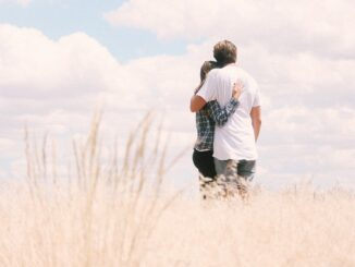 Žena a muž v objetí na louce
