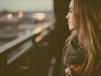 Šťastná dívka dívající se se z balkónu