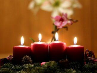Adventní věnec se čtyřmi zapálenými svíčkami.