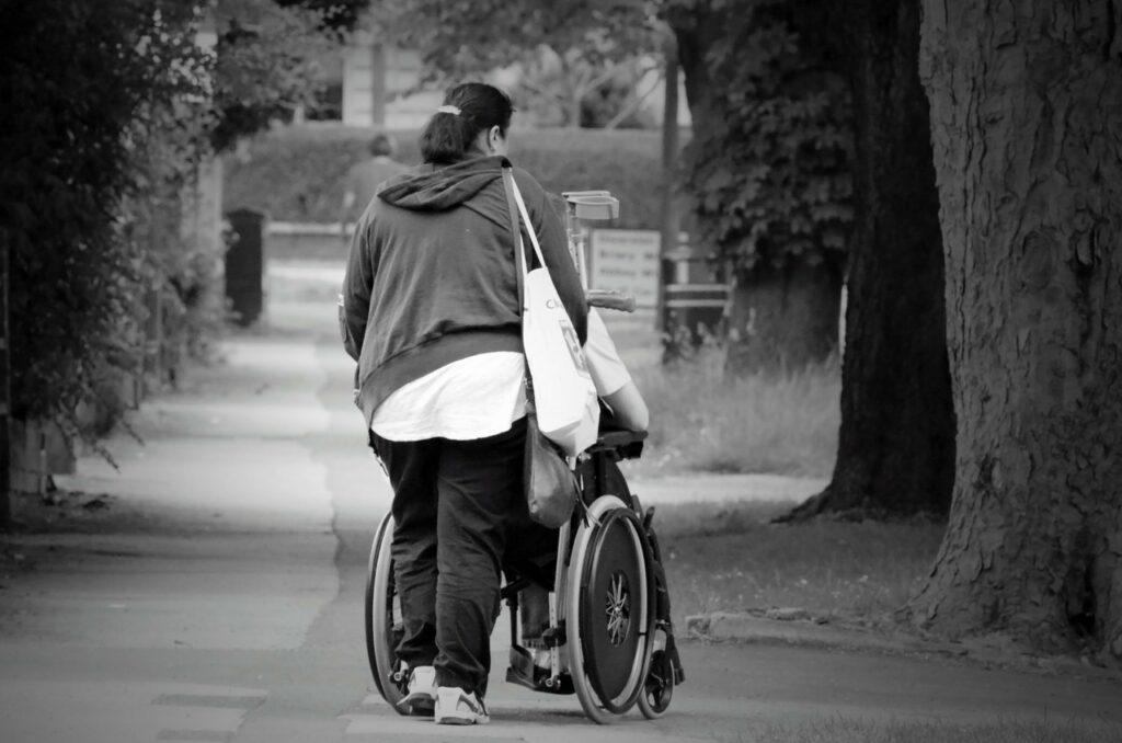 Žena tlačí invalidní vozík.
