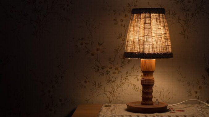 Rozsvícená stará lampička na nočním stolku