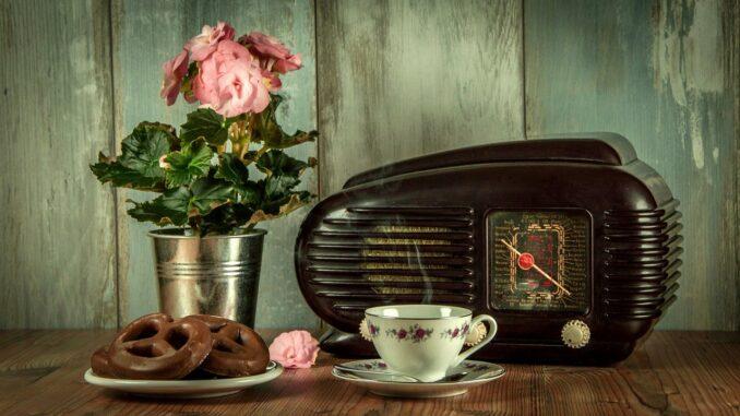 Staré radio, starý porcelánový hrníček s čajem a v pozdí květina.