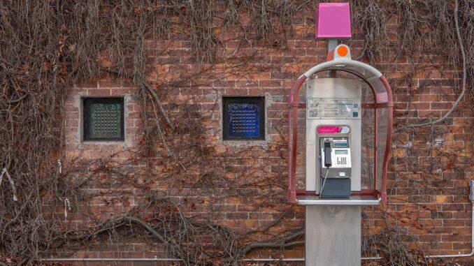 Telefonni budka před starým domem.