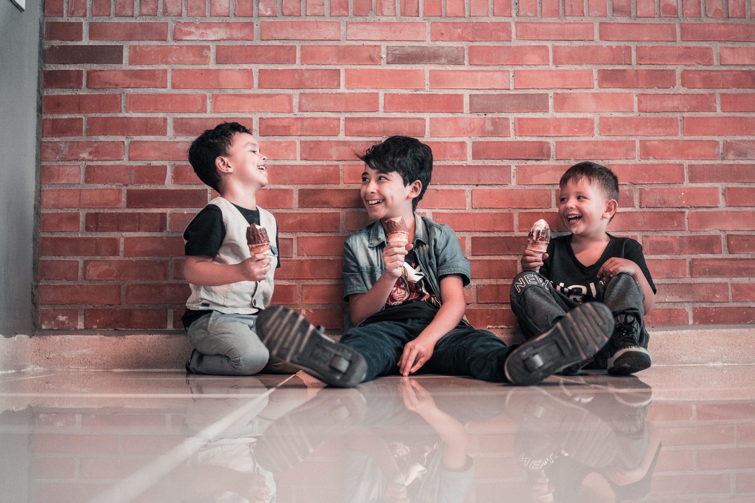 Tři kluci sedí na zemi a jí zmrzlinu.