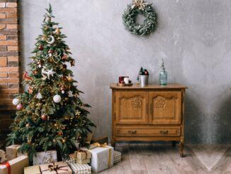 Vánoční stromeček s dárky zelený věnec na stěně a stará komoda