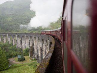 Červený vlak jedoucí po kameném vyjaduktu, v pozadí les.