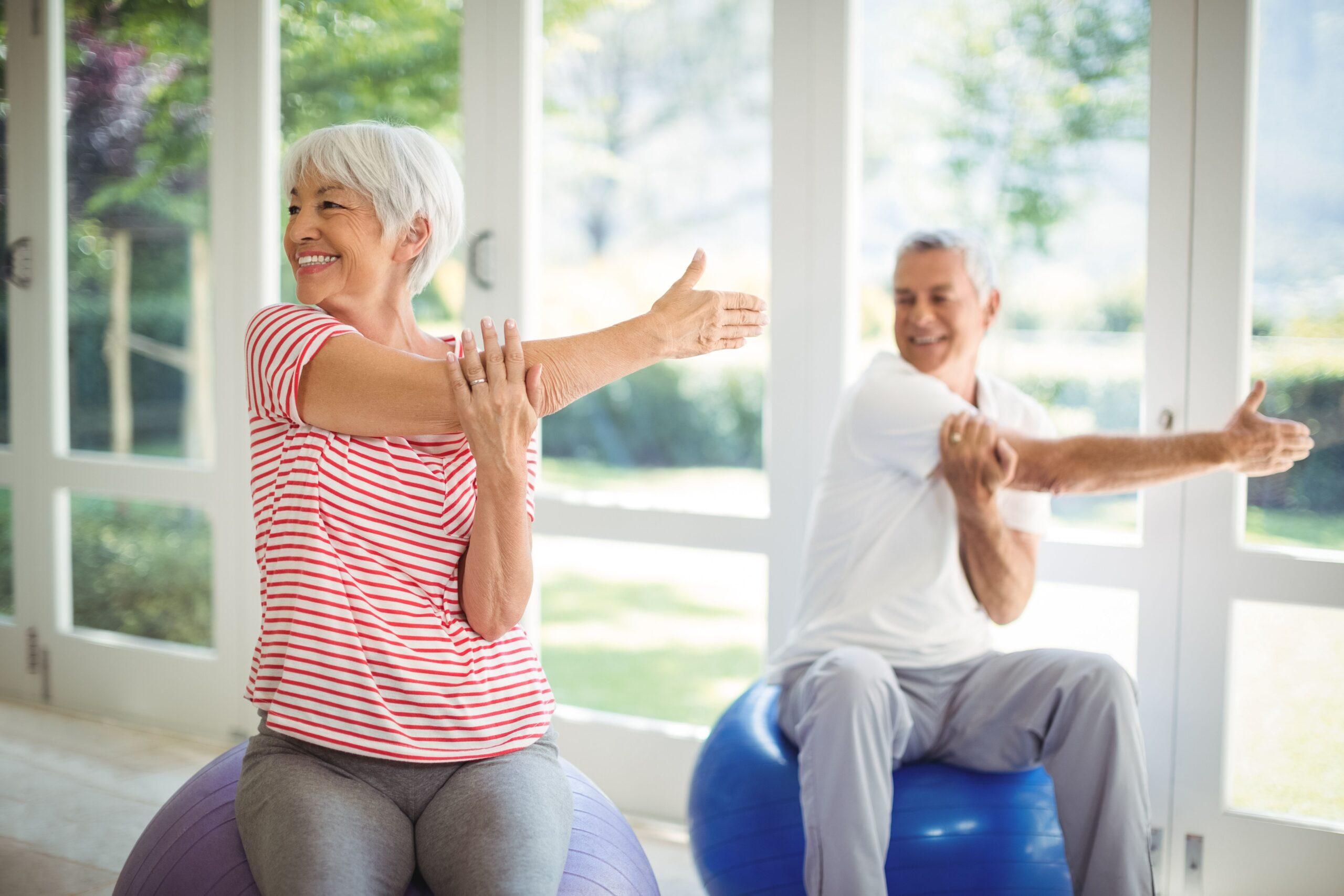Starší muž a starší žena se protahují před cvičením.