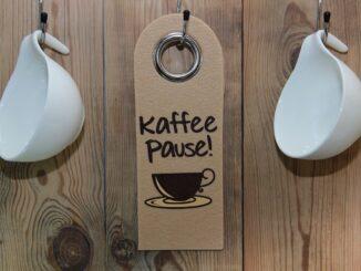Tři háčky na stěně, dva s pověšenými bílými hrnečky, jeden s cedulkou na které je napsané kaffee pause.