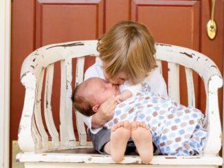 Dvě děti na laviččce, jede z nich je novorozené miminko.