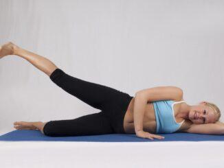 Žena cvičí vleže na boku.