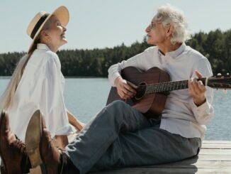 Senioři hrají na kytaru a zpívají.