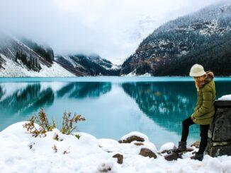Žena stojí u horského jezera v zimě.