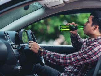 Muž při řízení popíjí pivo z lahve.