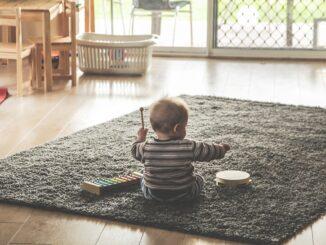 Dítě hraje na tamburínu a xylofon.