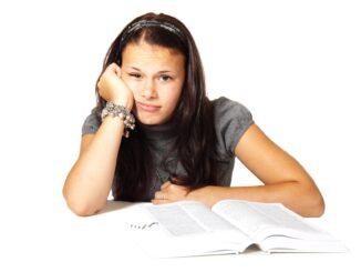 Dívka se nudí nad učebnicí.