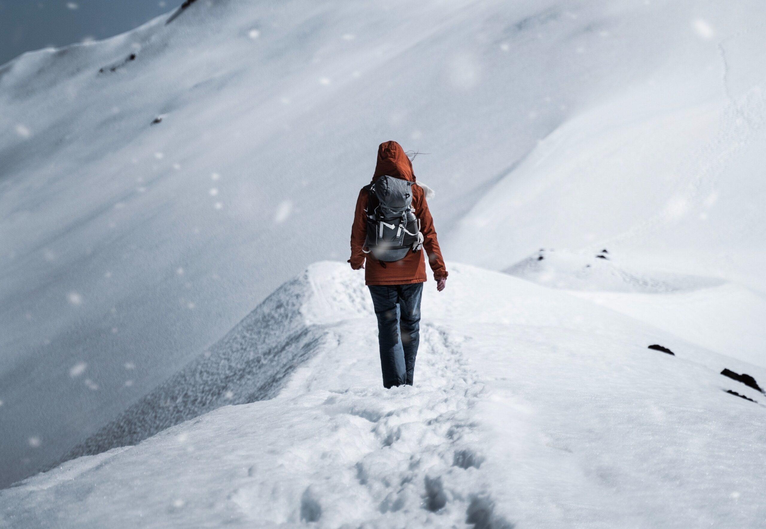Žena se prochází po hřebeni zasněženého kopce.