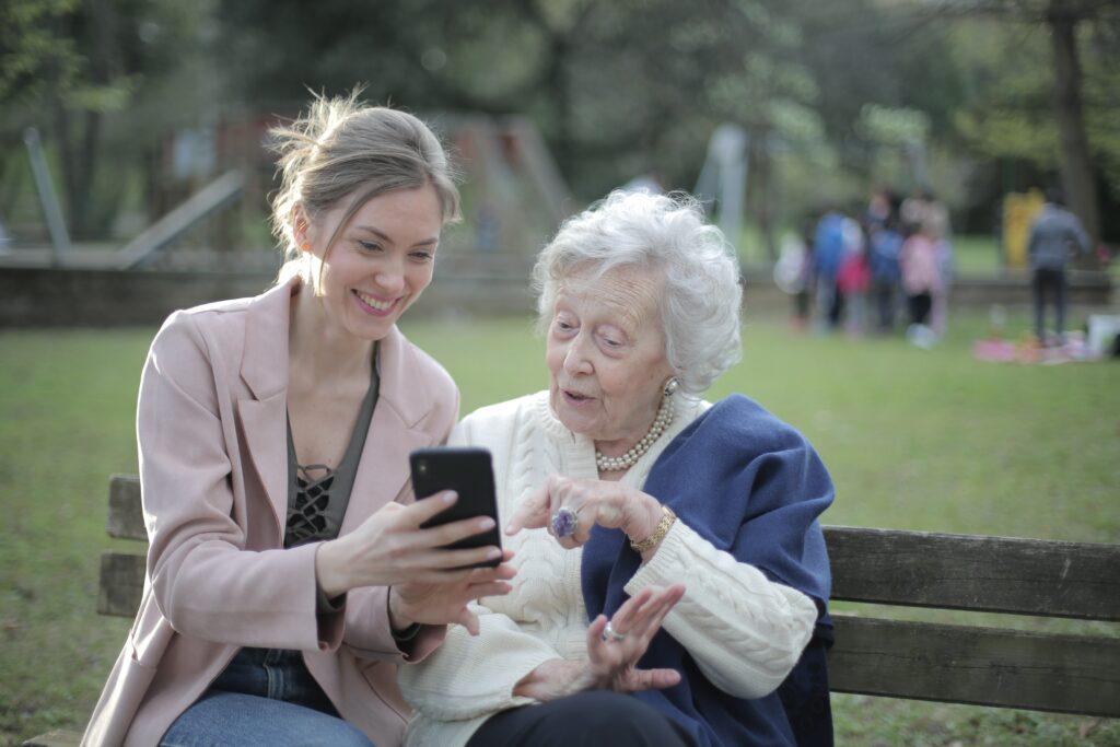 Mladá žena se seniorkou nastavují mobilní telefon.