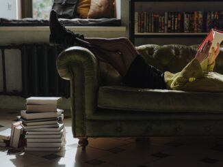 Hromada knih vedle gauče a dívka co na gauči čte.