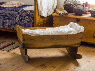 Stará dřevěná kolébka s bílými peřinkami