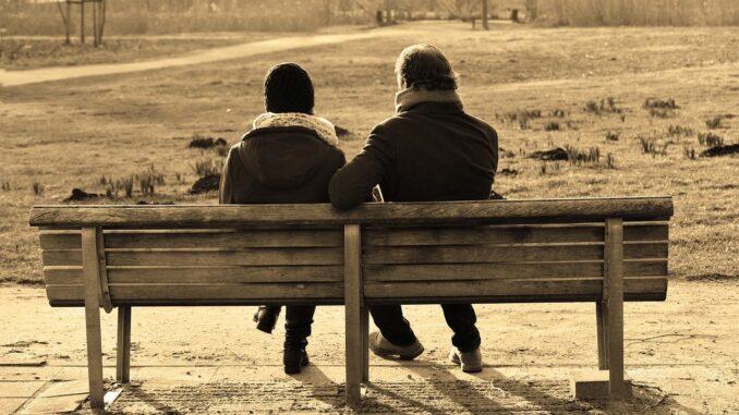 Dva lidí sedí v zimě na laviččce.