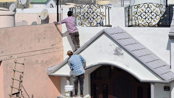 Dva muži malují bílou barvou dům.