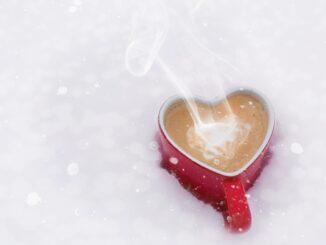 Hrnek s kávou ve tvaru srdce, položený ve sněhu.
