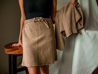 Pohled na dívku v bavlněné sukni co přes ruku má přehozené sako stejné barvy a materiálu
