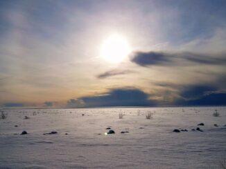 zasněžené pole a východ slunce.