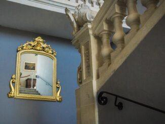 zrcadlo nad historickým schodištěm