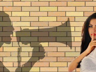 žena co naznačuje ticho a stín megafonu na zdi.