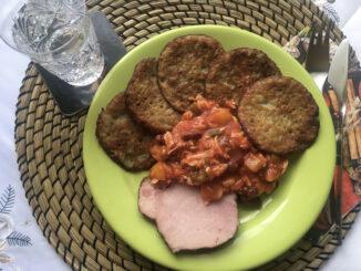 Bramboráky, fazolový salát a uzené maso.