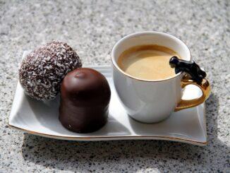 Hrnek s kávou a pralinky.