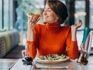 Žena se zamilovaně dívá na jídlo.