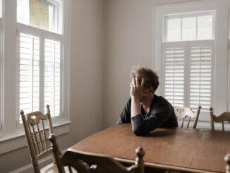 Osamělý muž sedí u stolu.