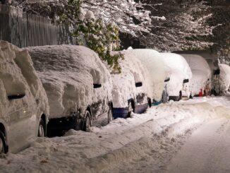 Zasněžená zaparkovaná auta kolem silnice