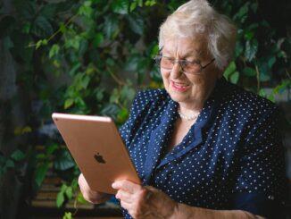 Starší žena volá přes tablet.