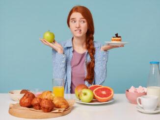 Dívka váhá mezi dietním a sladkým jídlem.