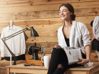 Žena se směje u šicího stroje.