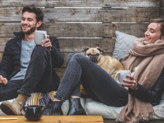 Muž a žena sedí s kávou a psem venku.