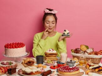 Mlsná dívka sedí u stolu plného dezertů.