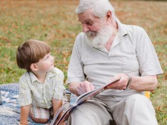 Dědeček s vnukem si čtou v parku.
