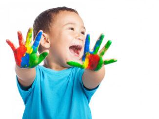 Dítě s pomalovanými dlaněmi.